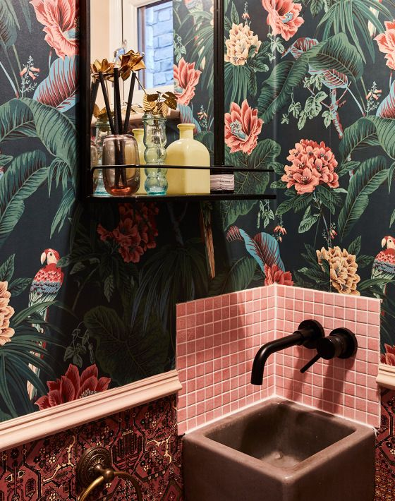 a maximalist bathroom with dakr floral wallpaper, pink tiles, a pink sink, black fixtures and a black shelf