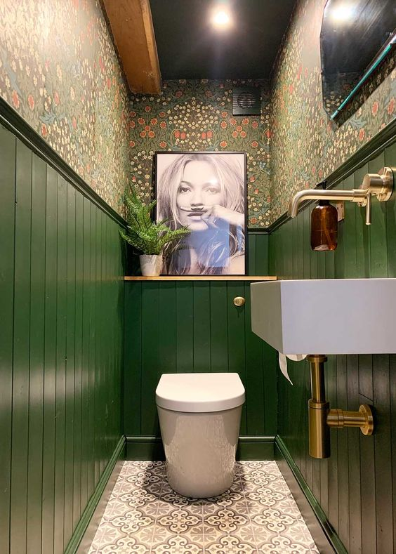 a maximalist bathroom with floral wallpaper, green paneling, an artwork and a statement artwork and brass touches