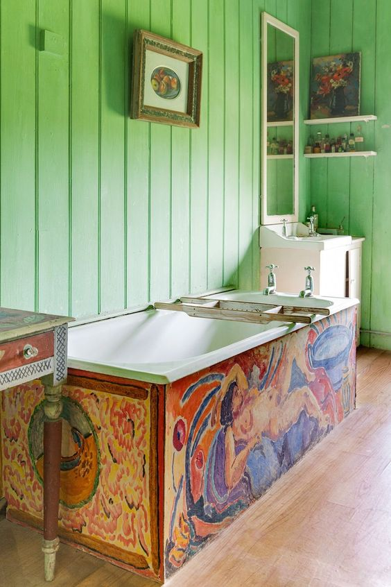 a maximalist bathroom with green planked walls, a colorful bathtub, a painted sink stand, pretty artworks and chic