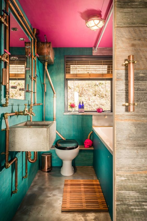 a maximalist bathroom with green walls and a hot pink ceiling, a concrete floor and a sink, copper exposed pipes and a skull