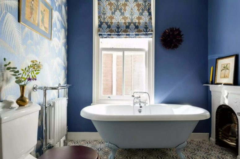a maximalist bathroom with navy walls and an accent tropical one, a fireplace and a blue tub, a printed curtain and a stained stool