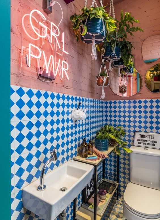 a maximalist bathroom with pink brick walls, blue and white checked tiles, a console table, potted greenery, a neon sign and mirrors