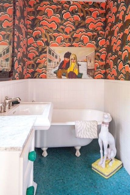 a maximalist bathroom with white paneling and bold printed wallpaper, blue tiles on the floor, with artworks and a dog