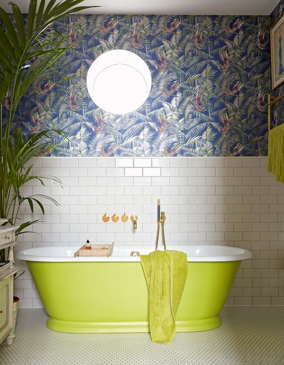 a maximalist bathroom with white subway tiles, dark tropical leaf wallpaper, a neon green bathtub and towels, a statement plant