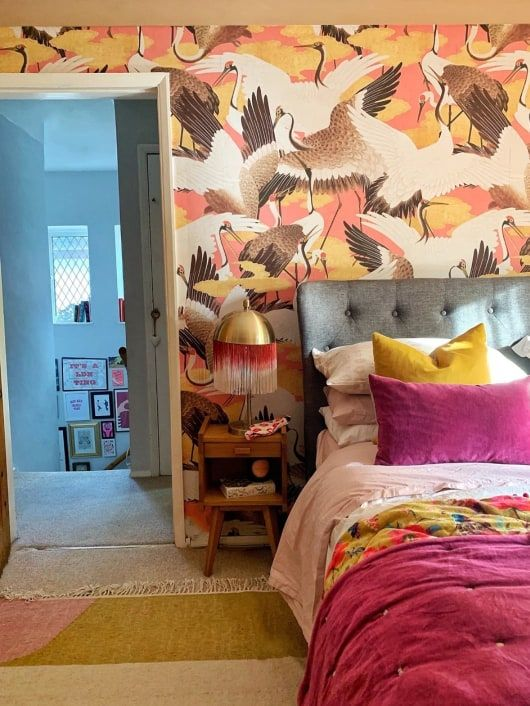 a maximalist bedroom with a bird printed wall, a grey bed, bright bedding and a rug, mid-century modern nightstands