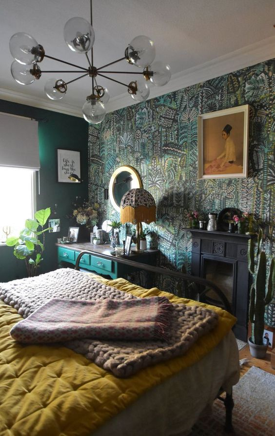 a maximalist bedroom with green walls and a botanical accent one, a black fireplace, a green console, a metal bed, bright bedding and a mirror
