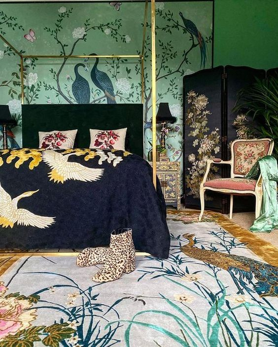 a maximalist bedroom with green walls with painting, a dark bed and a screen, a refined chair and amazing printed textiles that add chic