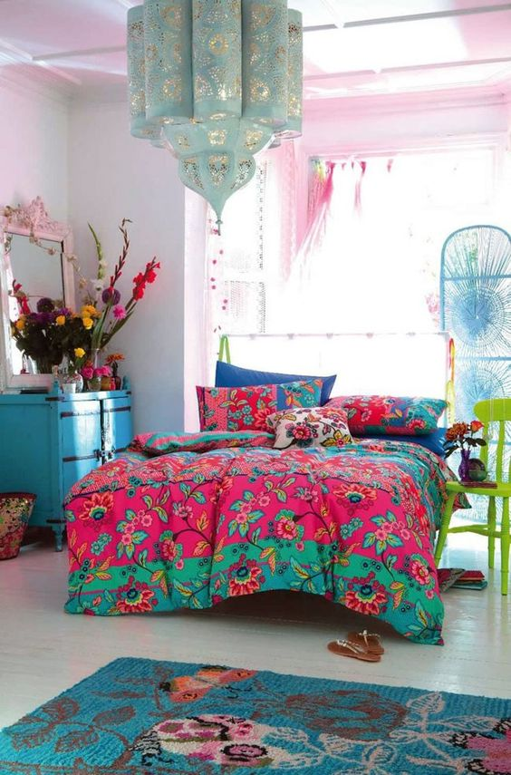 a maximalist bedroom with pink walls, a bed, a blue chest of drawers, a green chair, colorful bedding and bold blooms plus a lovely pendant lamp