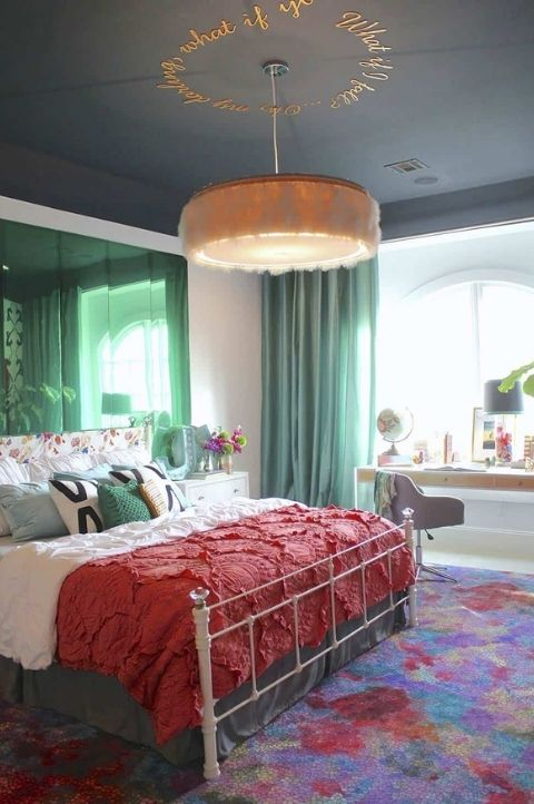 a maximalist bedroom with simple furniture, green mirrors and curtains, a colorful rug and bold bedding plus a fluffy chandelier