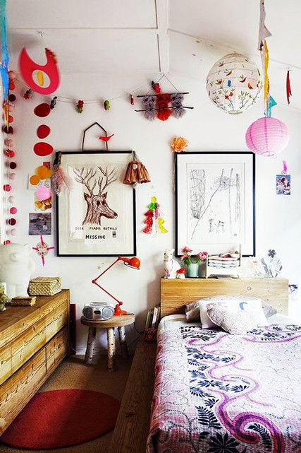 a maximalist bedroom with wooden furniture, bright lamps and artworks, bold bedding for much fun