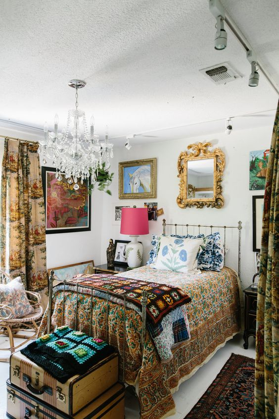 a maximalist guest bedroom with a metal bed, a rattan chair, vintage nightstands, floral textiles and a gallery wall