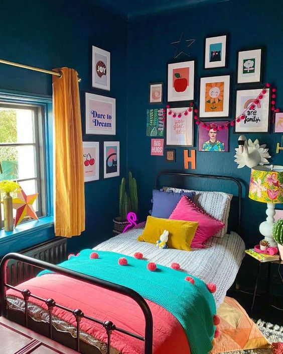 a maximalist guest bedroom with a metal bed, navy walls, a colorful gallery wall, a bright floral lamp and yellow curtains, colorful bedding
