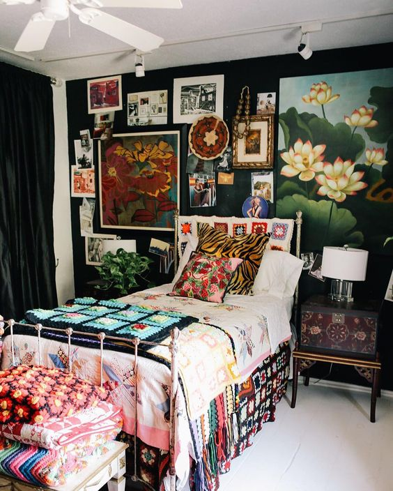 a maximalist guest bedroom with black walls, a metal bed, a refined inlaid nightstand, a bold gallery wall and colorful textiles
