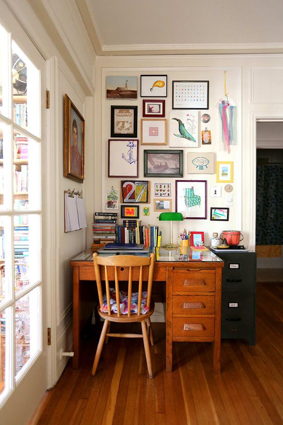 a maximalist home office wiht a vintage desk and chair, a colorful gallery wall and bold books and a table lamp