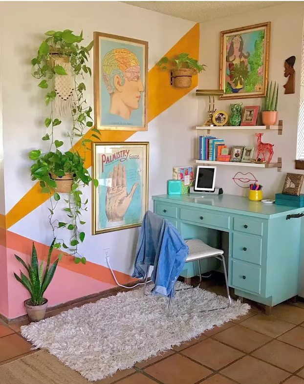 a maximalist home office with a color block accent wall, a turquoise desk, floating shelves, colorful art and lots of potted plants