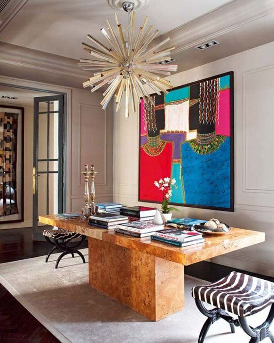 a maximalist home office with a large shared desk, colorful books, a bold statement artwork, printed chairs and a sunburst lamp