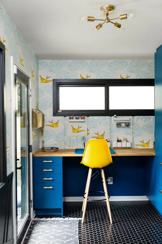 a maximalist home office with a penny tile floor, a bright blue desk, pretty printed wallpaper, a yellow stool and a gilded chandelier