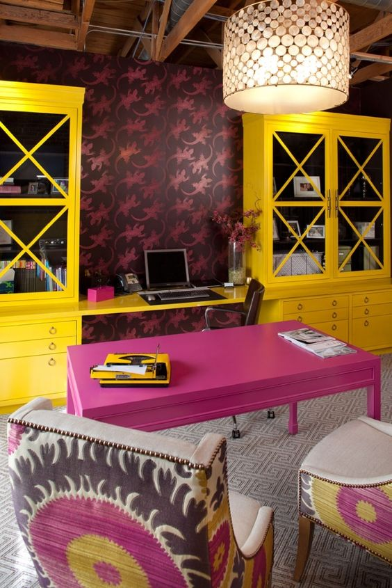 a maximalist home office with bold wallpaper, a hot pink desk and bold yellow storage units, colorful chairs and a pendant lamp
