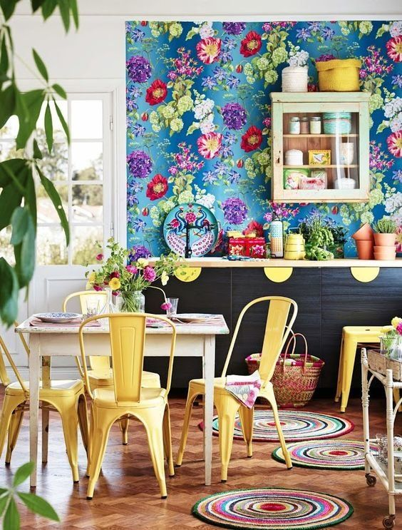 a maximalist kitchen with a blue floral wall, dark cabinets and yellow touches, colorful rugs and potted plants