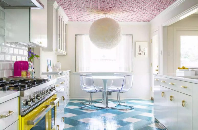 a maximalist kitchen with a bold blue printed floor, a bright yellow cooker, a colorful ceiling and a fluffy pedant lamp is a fun space