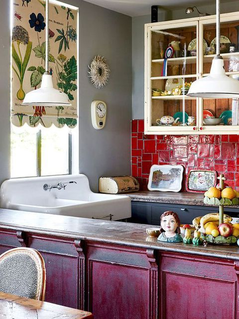 a maximalist kitchen with a hot pink kitchen island, red tiles on the backsplash, a botanical curtain and creamy and black cabinets