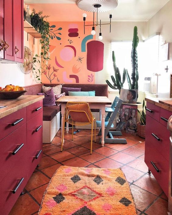 a maximalist kitchen with an orange wall, fuchsia cabinets, a mid-century modern chandelier and bold textiles