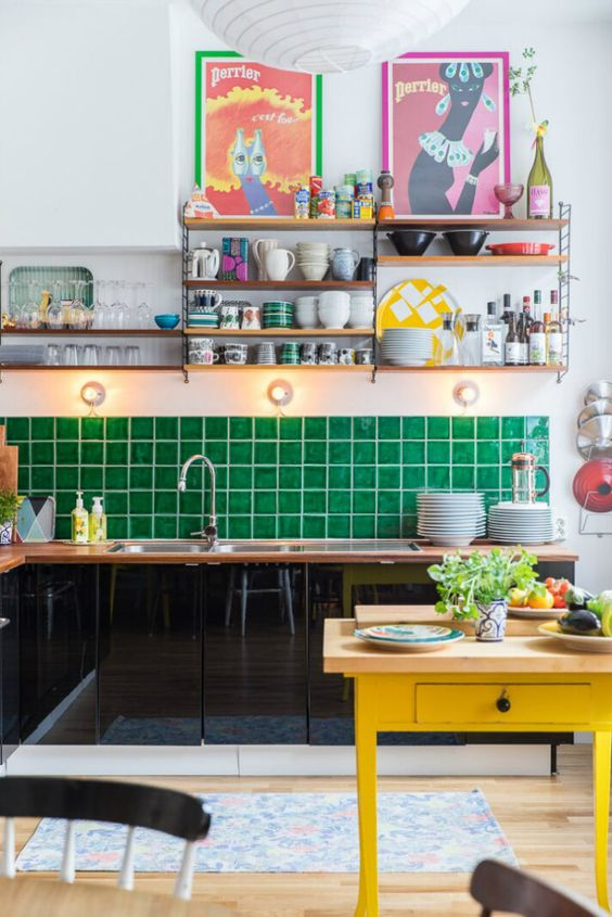 a maximalist kitchen with black sleek cabinets, an emerald tile backsplash, a yellow table, colorful artworks and open shelves