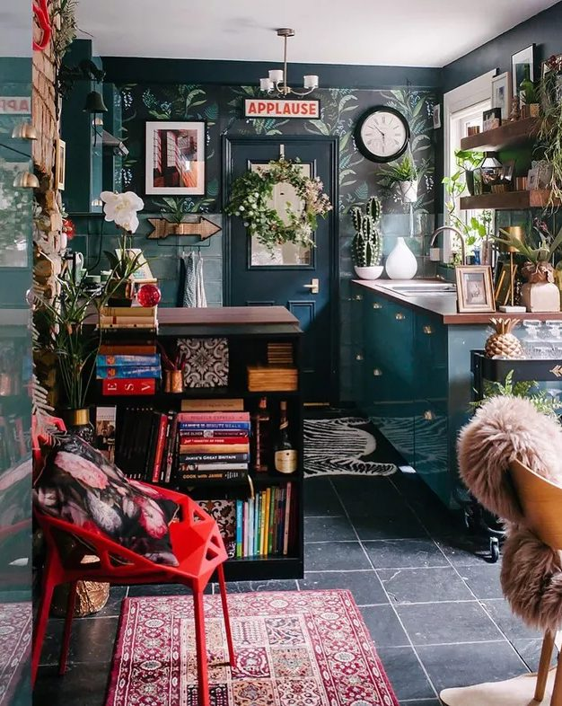 a maximalist kitchen with dark and tropical leaf walls, blue cabinets and a black kitchen island, a red chair and potted plants