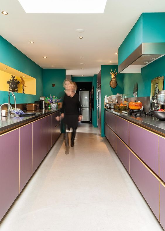 a maximalist kitchen with green walls and a hood and purple lower cabinets, a yellow niche and taxidermy