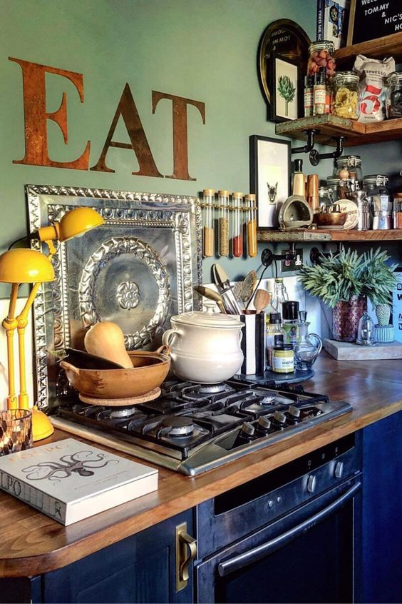 a maximalist kitchen with green walls and navy cabinets, butcherblock countertops, rough wooden shelves and a yellow lamp