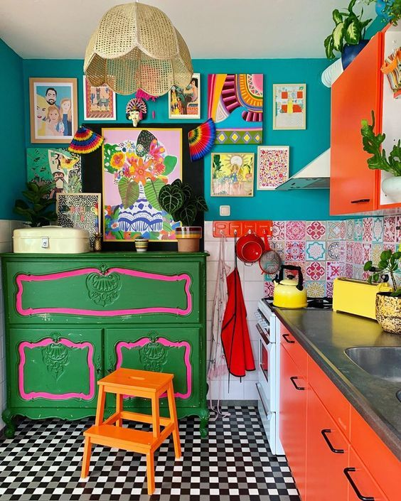 a maximalist kitchen with teal walls, red cabinets, a green dresser, a colorful gallery wall and a checked floor