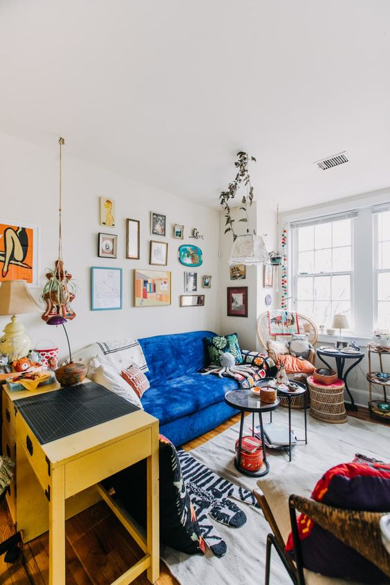 a maximalist living room with a bold blue sofa, a yellow console table, a bright gallery wall, a rattan chair and round tables