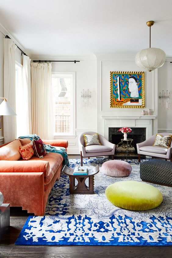 a maximalist living room with a coral sofa, a bold blue rug, pastel ottomans, lilac chairs and a bold artwork