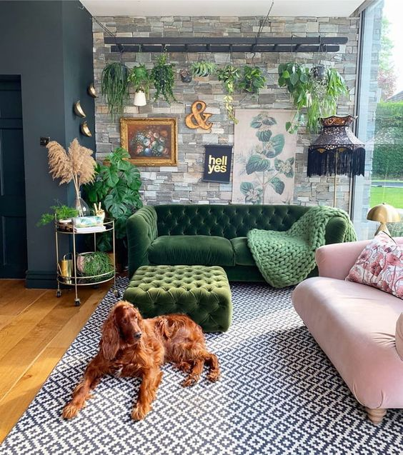 a maximalist living room with a faux stone wall, a green and a pink sofa, a green ottoman, a printed rug and potted plants is chic