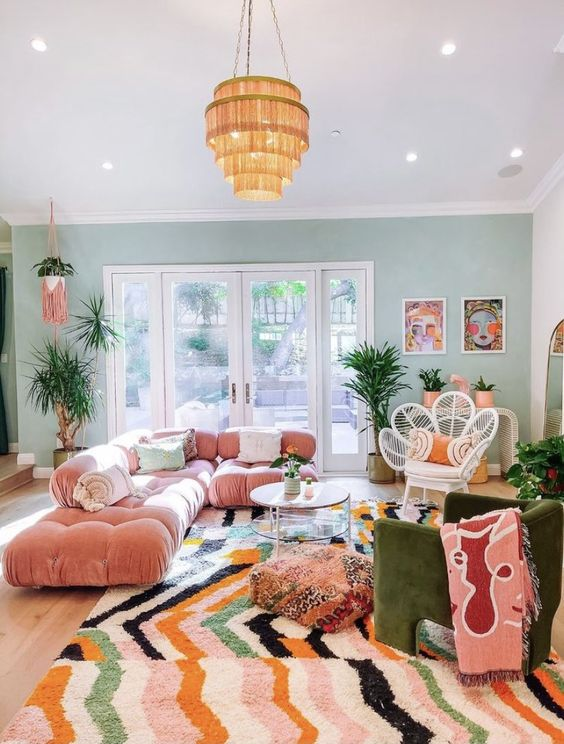 a maximalist living room with a green accent wall, a pink sofa, a green chair, a bright rug and a glazed tiered table