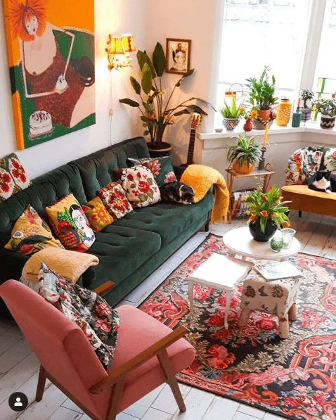 a maximalist living room with a green sofa and mustard and pink chairs, a bold rug and colorful pillows, potted plants and candleholders