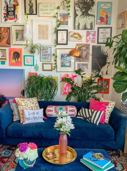a maximalist living room with a large and bold gallery wall, with a bold blue sofa, statement plants and a brass lamp and a tray