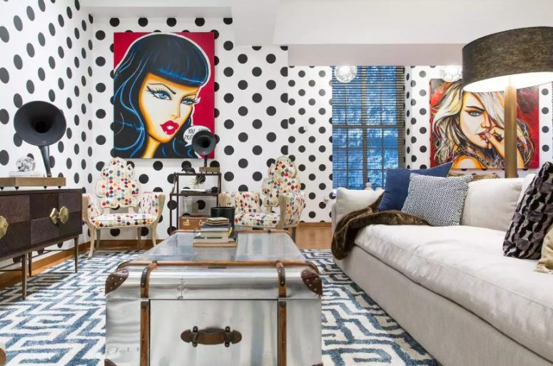 a maximalist living room with a neutral sofa, a metal suitcase as a table, polka dot chairs of quirky shapes, polka dot wlals and pop art pieces