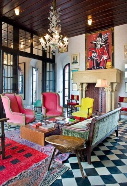 a maximalist living room with a non-working fireplace and a checked floor, pink chairs, a green sofa and colorful rugs plus bold artworks