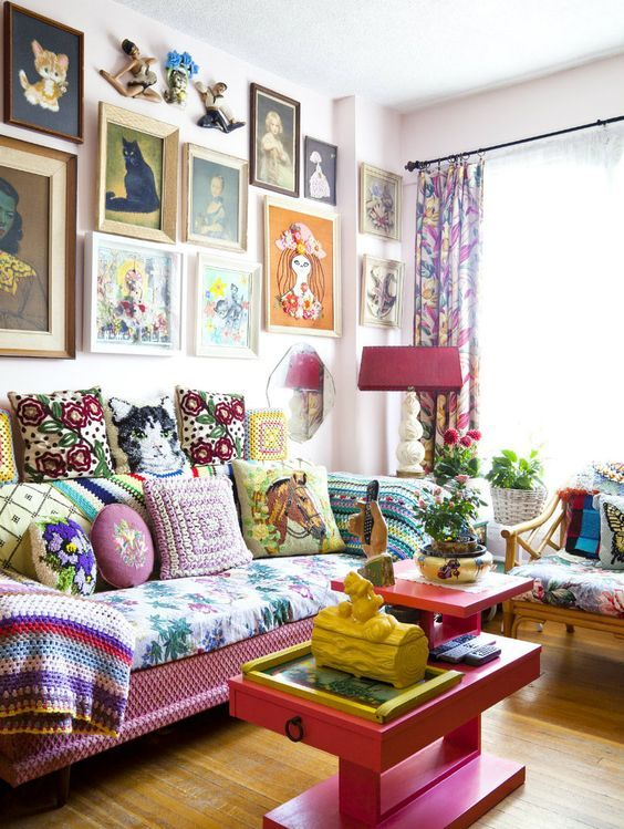 a maximalist living room with a pink sofa and a coffee table, a floral chair, a bright gallery wall and potted plants and blooms