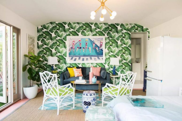 a maximalist living room with a tropical accnet wall, a grey sofa and neon chairs, a statement plant and a chandelier