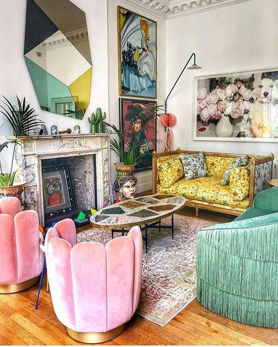 a maximalist living room with a yellow printed sofa, pink chairs and a green fringe sofa, bold artworks and a catchy mirror