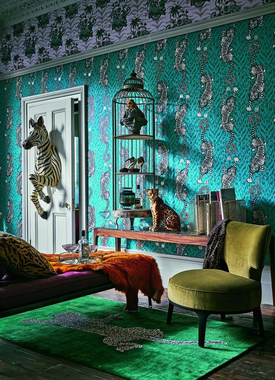 a maximalist living room with catchy green wallpaper, a cage with art and shoes, a leopard figurine and a zebra coming through the door, jewel tone furniture
