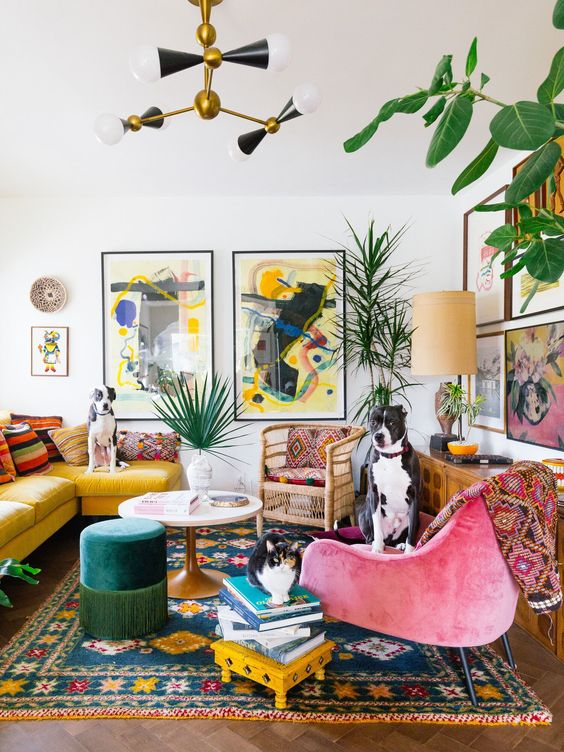 a maximalist living room with colorful furniture, rattan chairs, bright rugs, pillows and books and colorful gallery walls