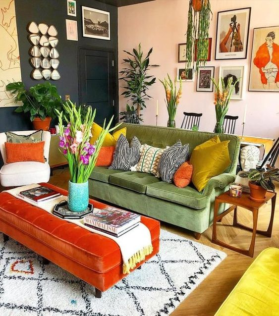 a maximalist living room with graphite grey and blush walls, a green sofa, an orange ottoman, colorful pillows and potted plants