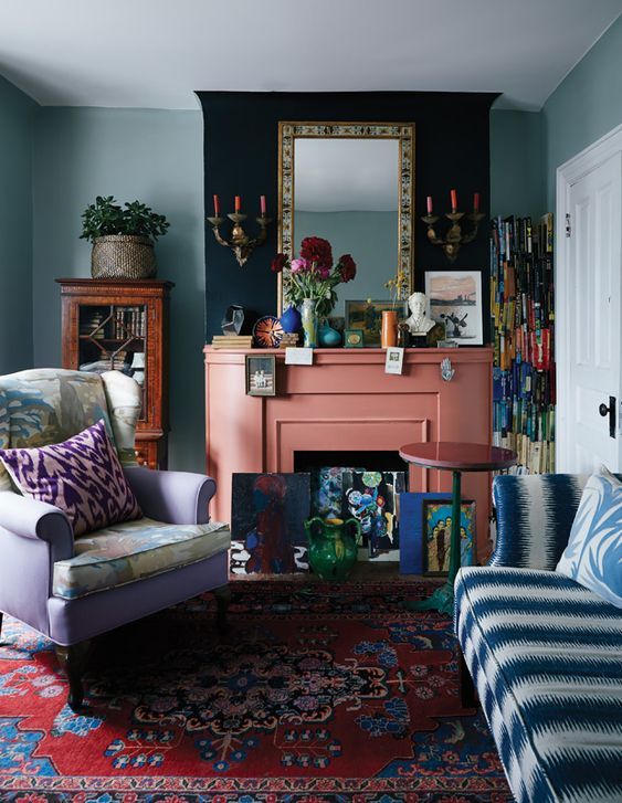 a maximalist living room with green walls, a lilac chair and a blue and white sofa, colorful pillows, a coral fireplace and bright accessories
