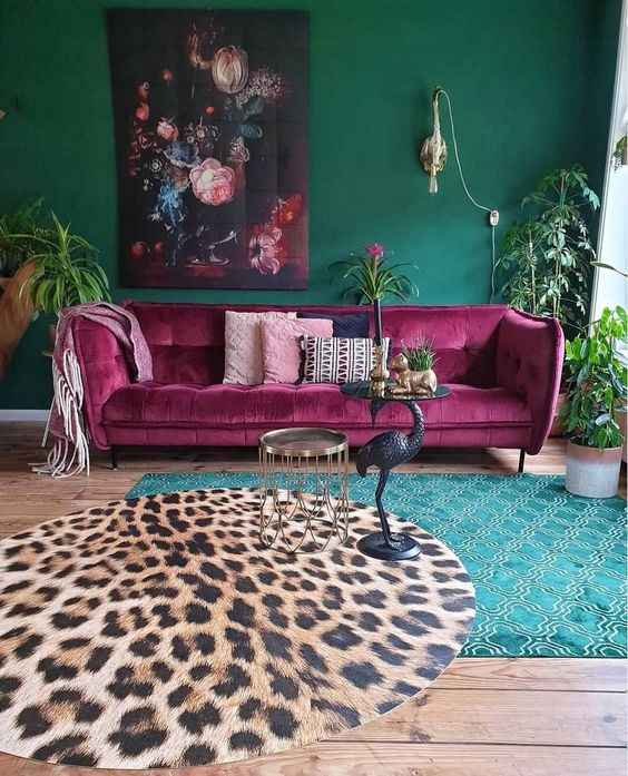 a maximalist living room with green walls, layered rugs, a fuchsia sofa, a bold artwork and potted greenery is chic