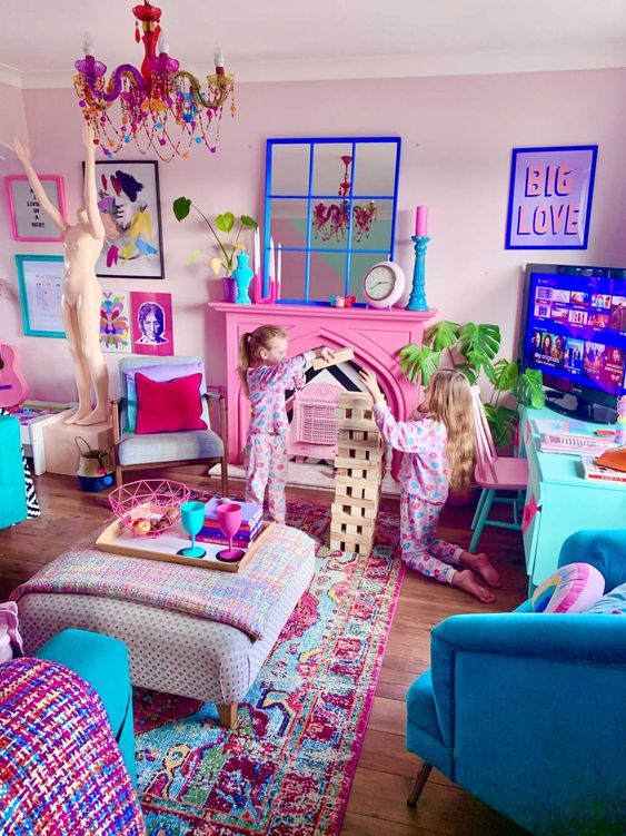a maximalist living room with light pink walls, a hot pink fireplace, blue furniture and colorful textiles, a pink chandelier and a colorful gallery wall