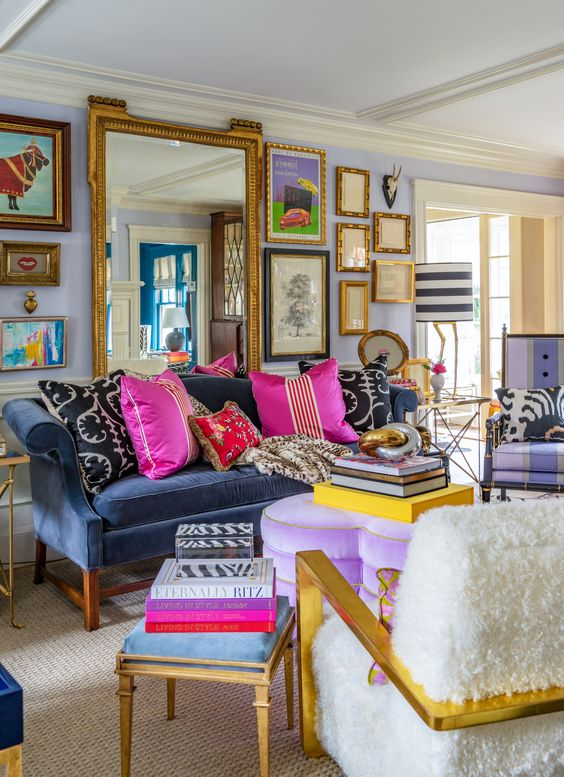 a maximalist living room with lilac walls, a navy sofa, a purple heart ottoman, colorful pillows and books and a gallery wall with a large mirror