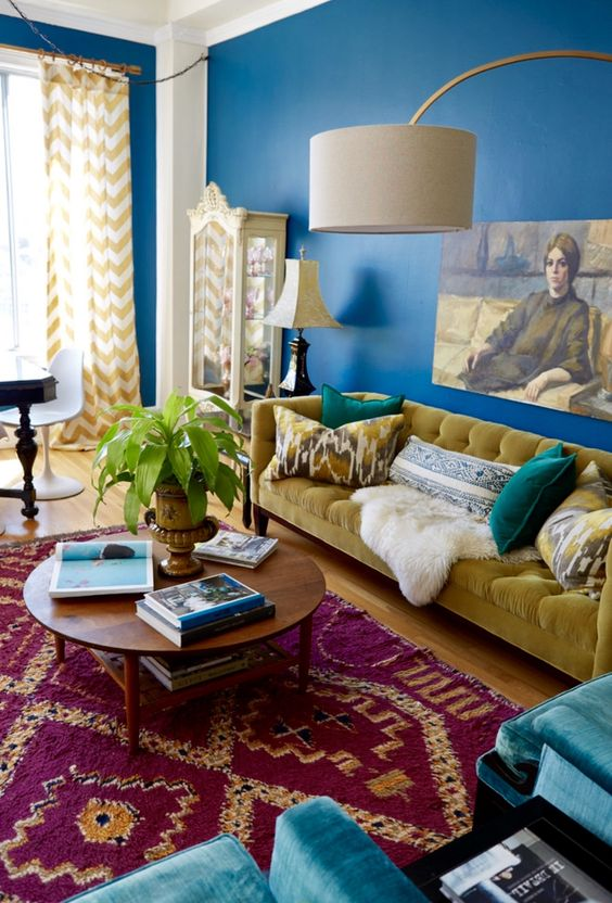 a maximalist living room with navy walls, a fuchsia printed rug, a mustard sofa and blue chairs and a bold artwork